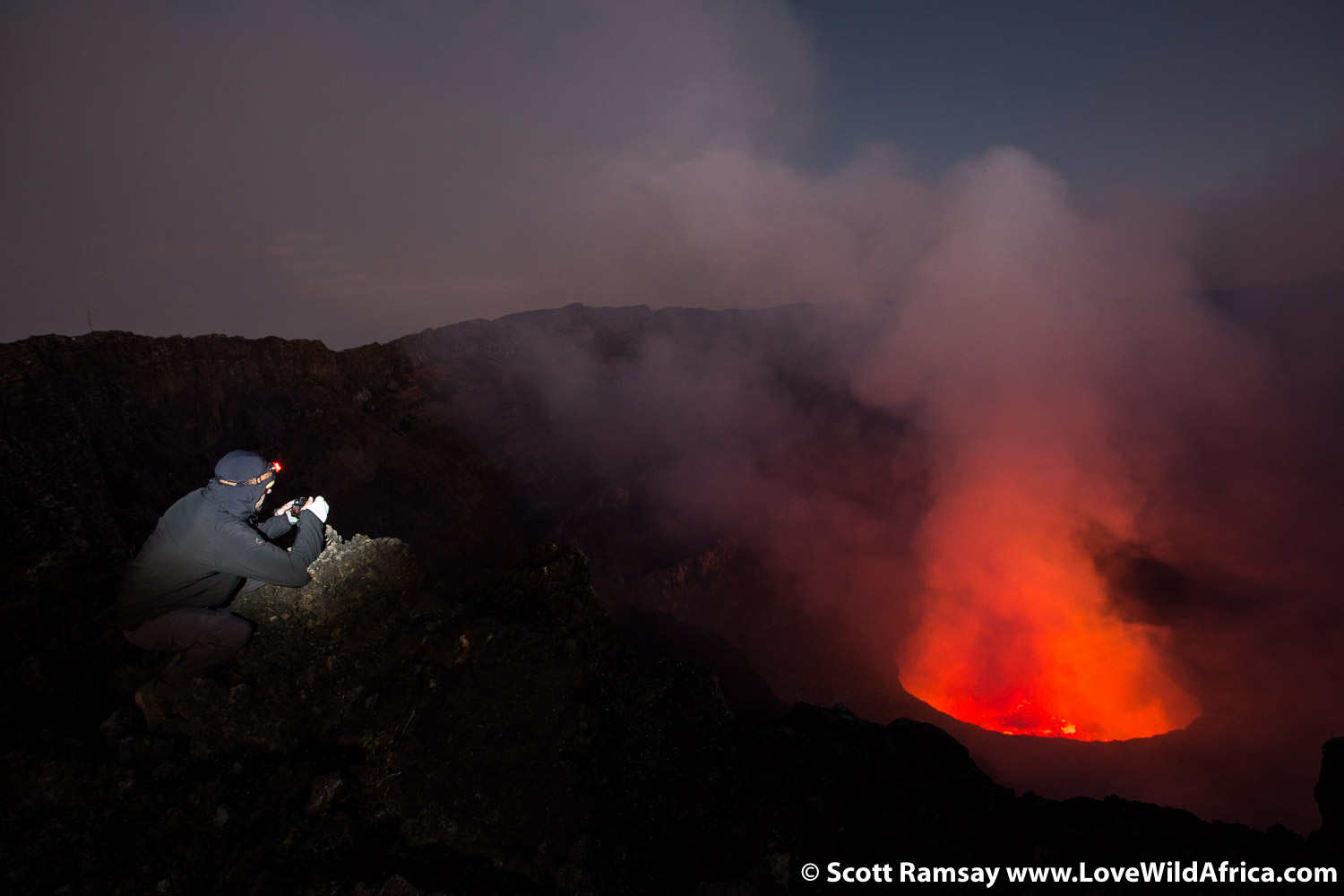 A hiker takes a photo of the lava lake of Mount Nyiragongo.