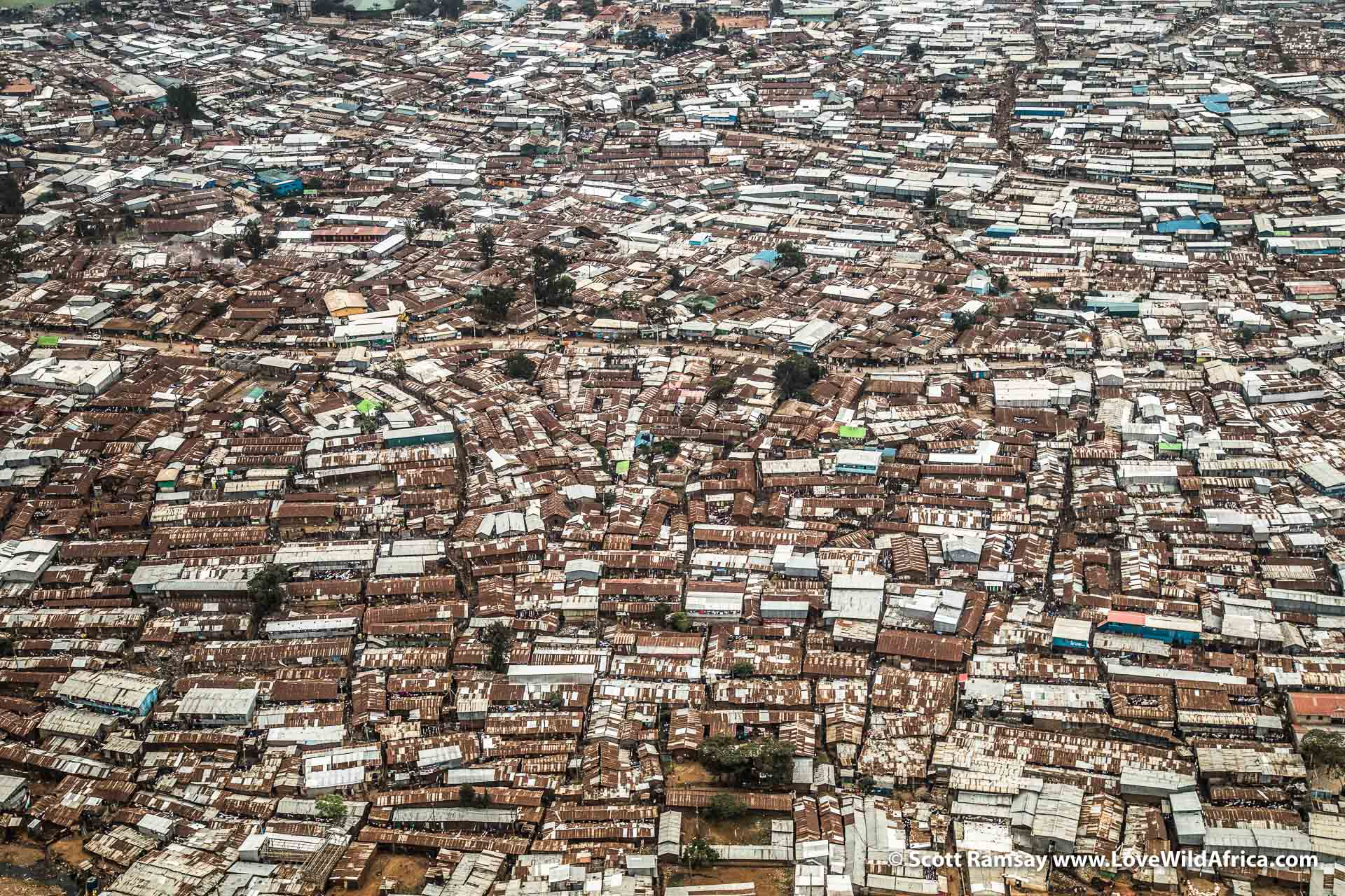 "This is one kind of Kenya. Flying from Nairobi to Laikipia, we passed over Kibera, the largst ""slum"" in Kenya's capital, about 7 kilometres from the city centre. About half a million people live here. Interestingly, while the highlands of Laikipia were leased out to World War I army officers, Kibera was originally allocated in the early 1900s by the colonial government to Nubian soldiers from Sudan who had served in the King's African Rifles, a regiment made up of African soldiers. Today the Kenyan government claims ownership of the land, and since 2009 has been trying to move people into highrise blocks elsewhere. By all accounts, it hasn't worked."