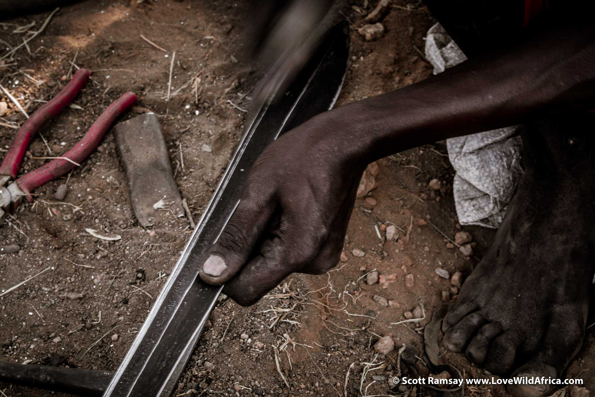 Smoothing and sharpening the blade...these swords are used for defending cattle from lions and other predators, and perhaps for skirmishes with obstreperous Turkana raiders.